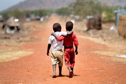 To drenge med ryggen til går og holder hinanden om skuldrene i flygtningelejr i Bidibidi