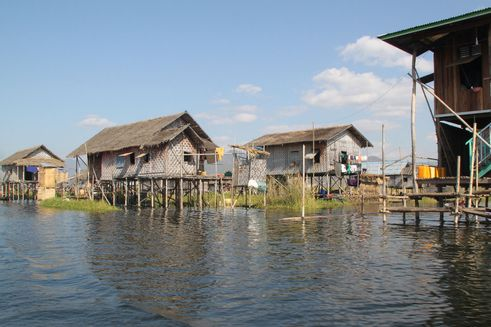 Stråhuse på stolper i vand