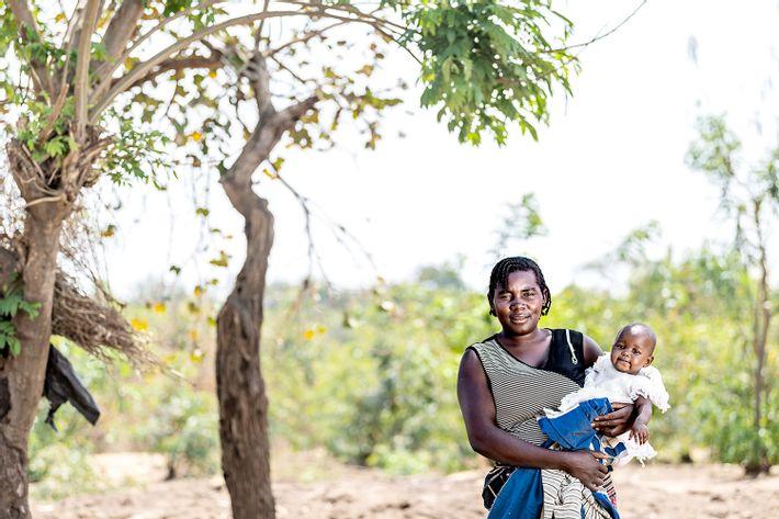 Glad kvinde med spædbarn på armen står udenfor og kigger mod fotografen