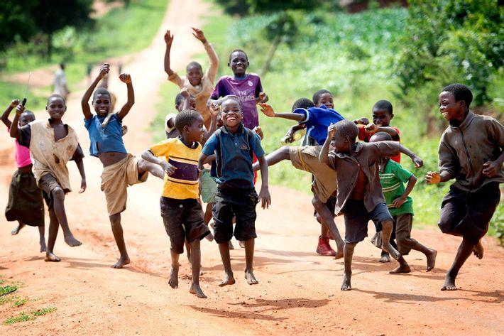 Stor gruppe drenge løber glade og hujende mod fotografen