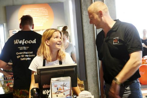 To Wefood frivillige snakker sammen foran kassen i butikken og er i godt humør.
