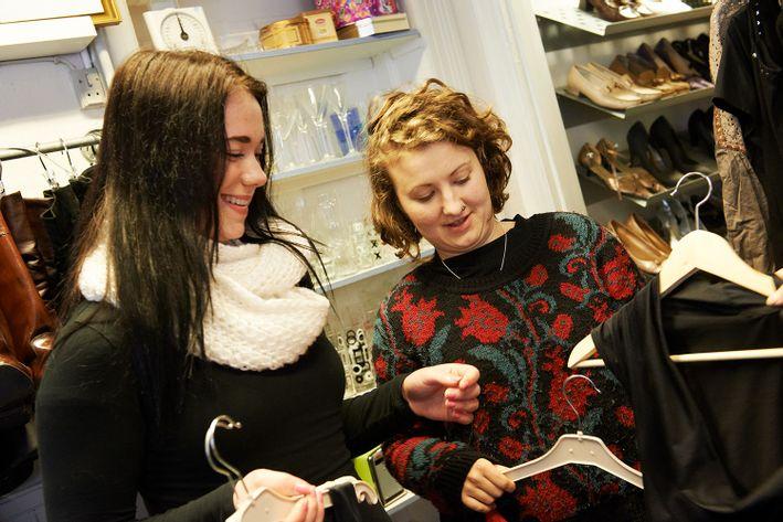 Unge kunder ser på tøj i genbrugsbutik