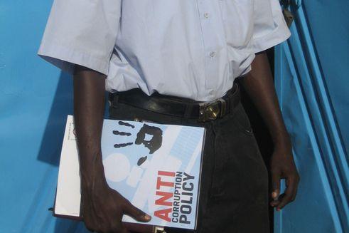 Mand står med mappe, hvor der står anti-korruptionspolitik på