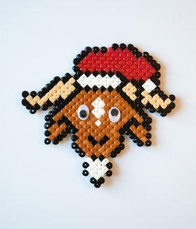En ged med en nissehue på lavet af perler.