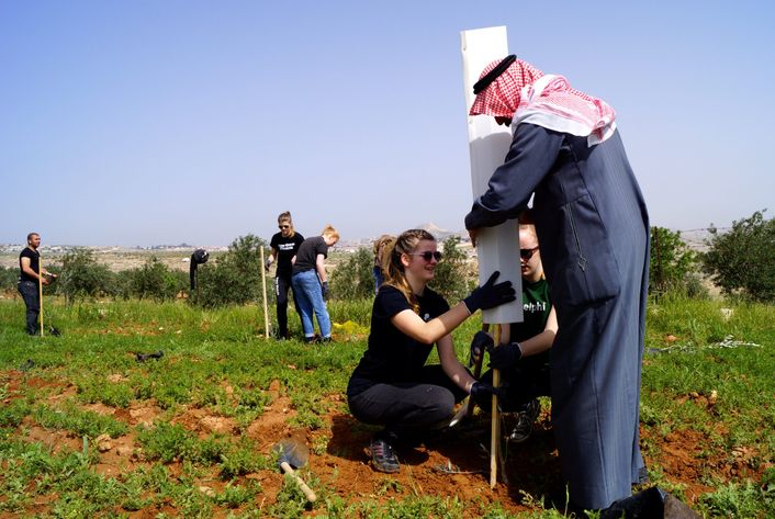 Eleverne og den palæstinensiske bonde hjælpes ad med at plante 400 træer på hans mark