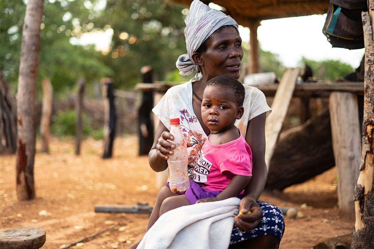 Barn sidder på skødet af sin mor i Zimbabwe