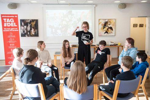 Ung kvinde fra TagDel-Karavanen underviser andre unge, der sidder i rundkreds rundt om hende på stole