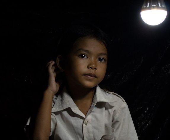 thida, en pige fra Cambodia, sidder under en solcellelampe