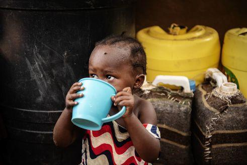 Lille pige drikker af en stor blå kop i flygtningelejren i Kakuma