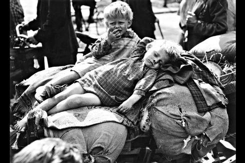 Sort hvid billede af to børn, der ligger på sække. Det ene barn sover og det andet barn græder