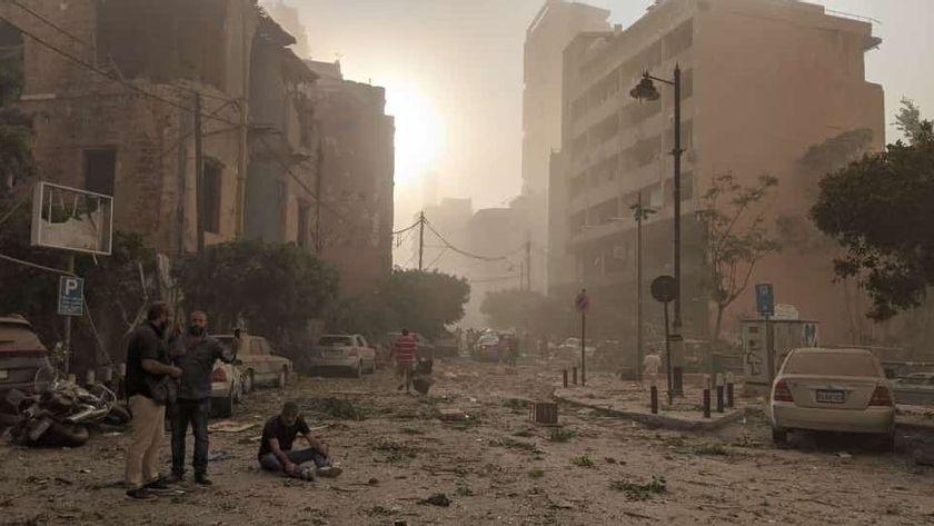En såret mand sidder midt på gaden, mens to andre står og taler ved siden af. Skilte er ødelagt og grene og møbler ligger spredt ud over gader og fortove.