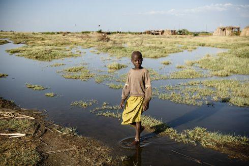 Aminit, pige fra Kenya i gul kjole står i vand