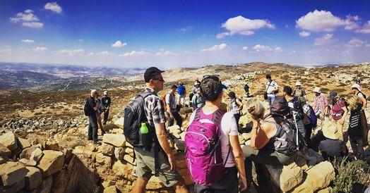En gruppe mennesker som står i klippet miljø på vandretur.